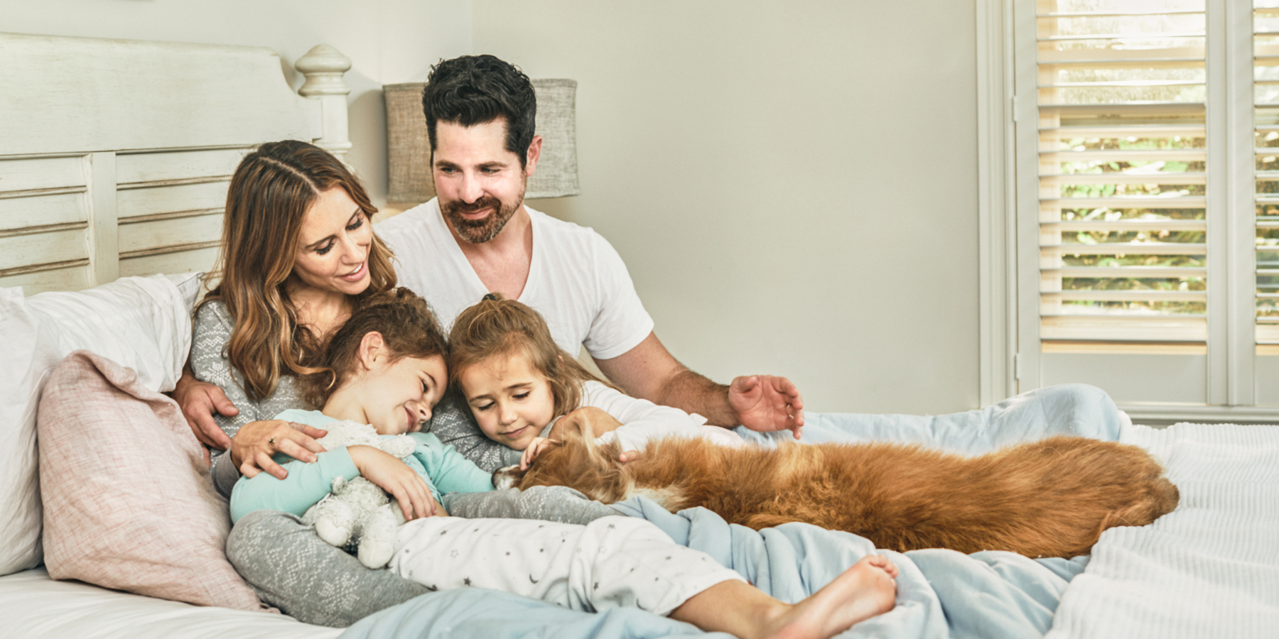 A husband and wife sitting on a bed holding their two daughters as they pet their dog