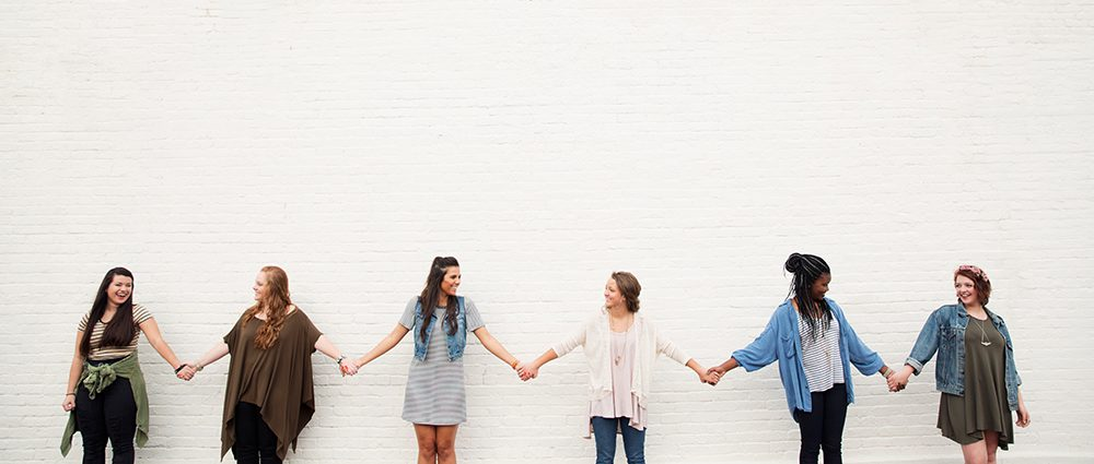 Six women holding hands in front of a white brick wall smiling