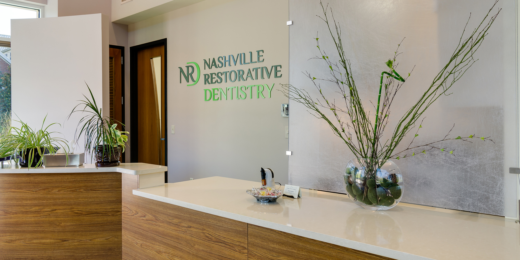 The entryway of Nashville Restorative Dentistry's office featuring the logo on the wall and plants sitting on the counter