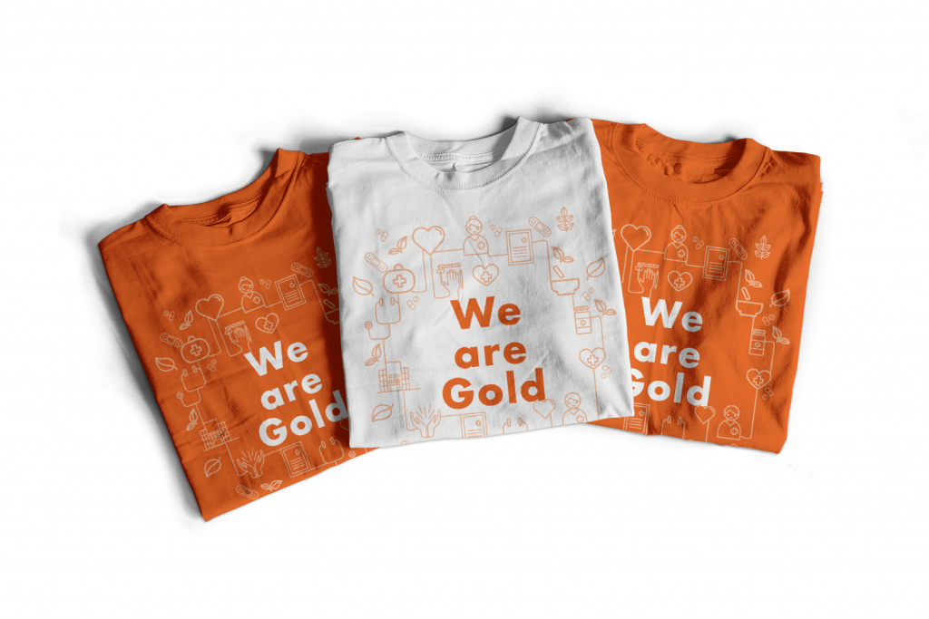 "Three folder shirts in orange and white that say ""We are gold"""