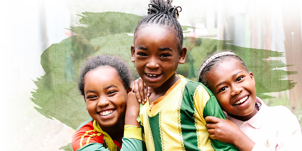 Three young girls in colorful clothing hugging and smiling.