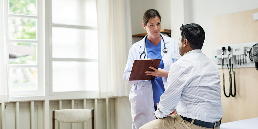 A female doctor with a clipboard talking to a male patient.