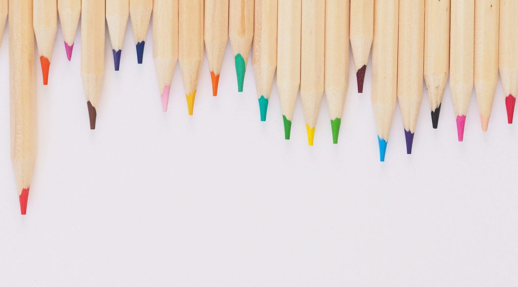 Wooden colored pencils lined up with a white background