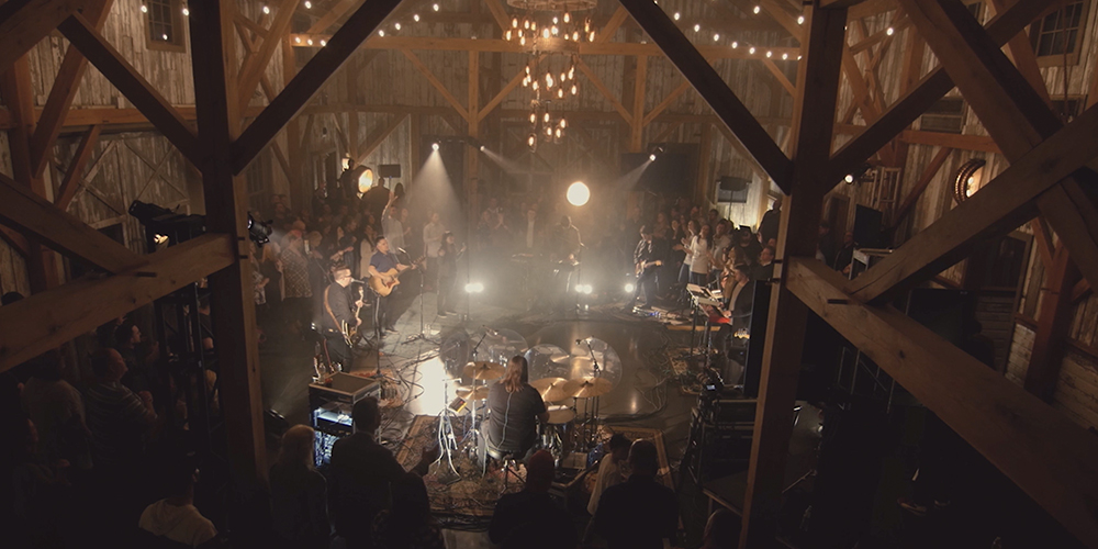 Photo of a band playing in a barn with people circled around listening to the music.