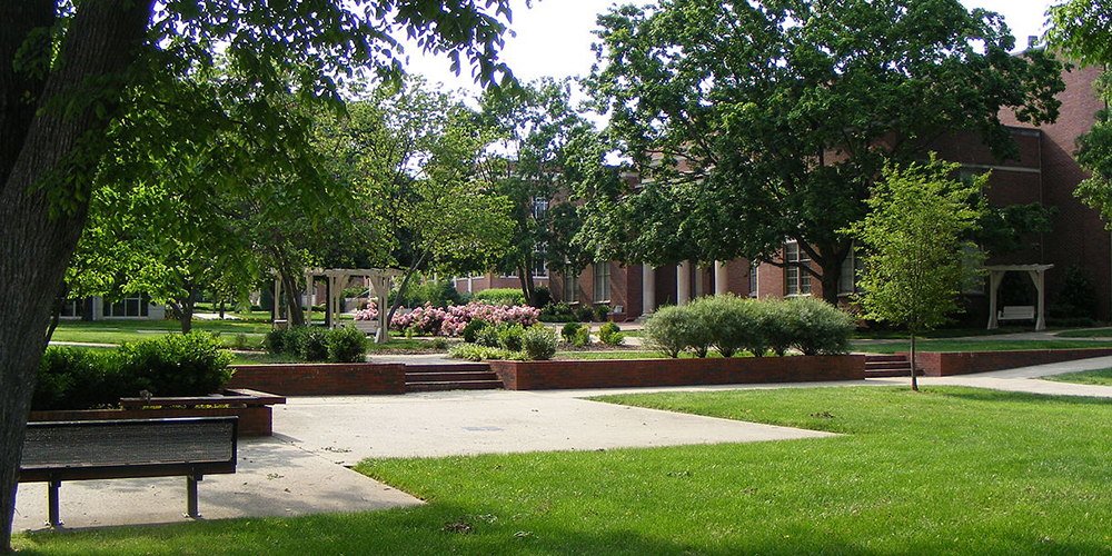 The quad at Lipscomb University filled with blooming trees and plants on a sunny day