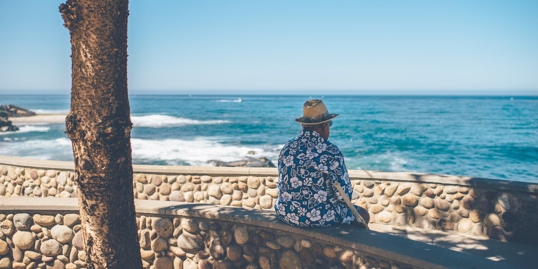 A man wearing a hat and Hawaiian shirt sitting on a bench as he looks out to the ocean with waves crashing in