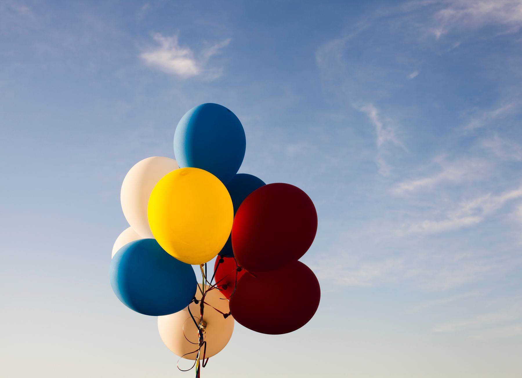 Several blue, red, yellow and white balloons against a cloudy sky.