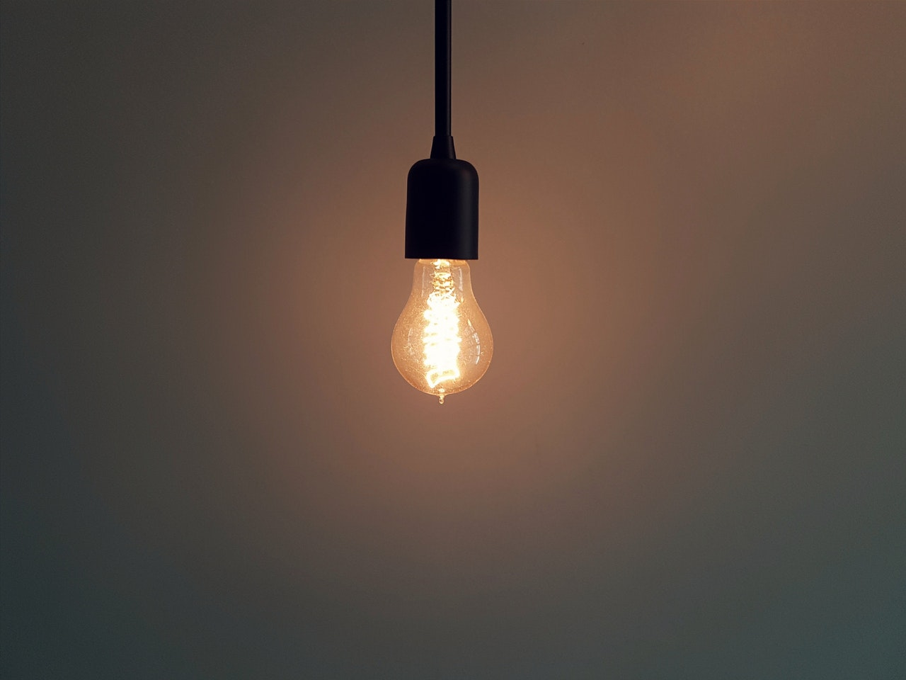 A lit lightbulb hanging on a pendant against a blank wall.