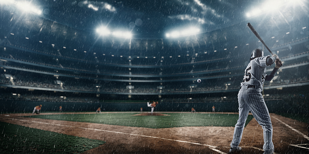 Baseball player about to swing the bat during a game in a stadium while it is raining.
