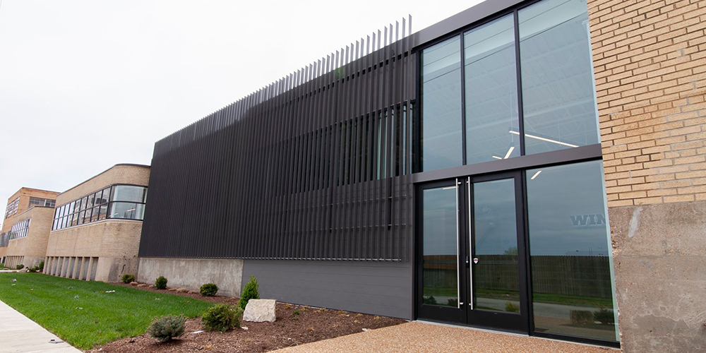 A photo of Win Warehouse. A brick warehouse with glass doors and a black metal facade on the front.