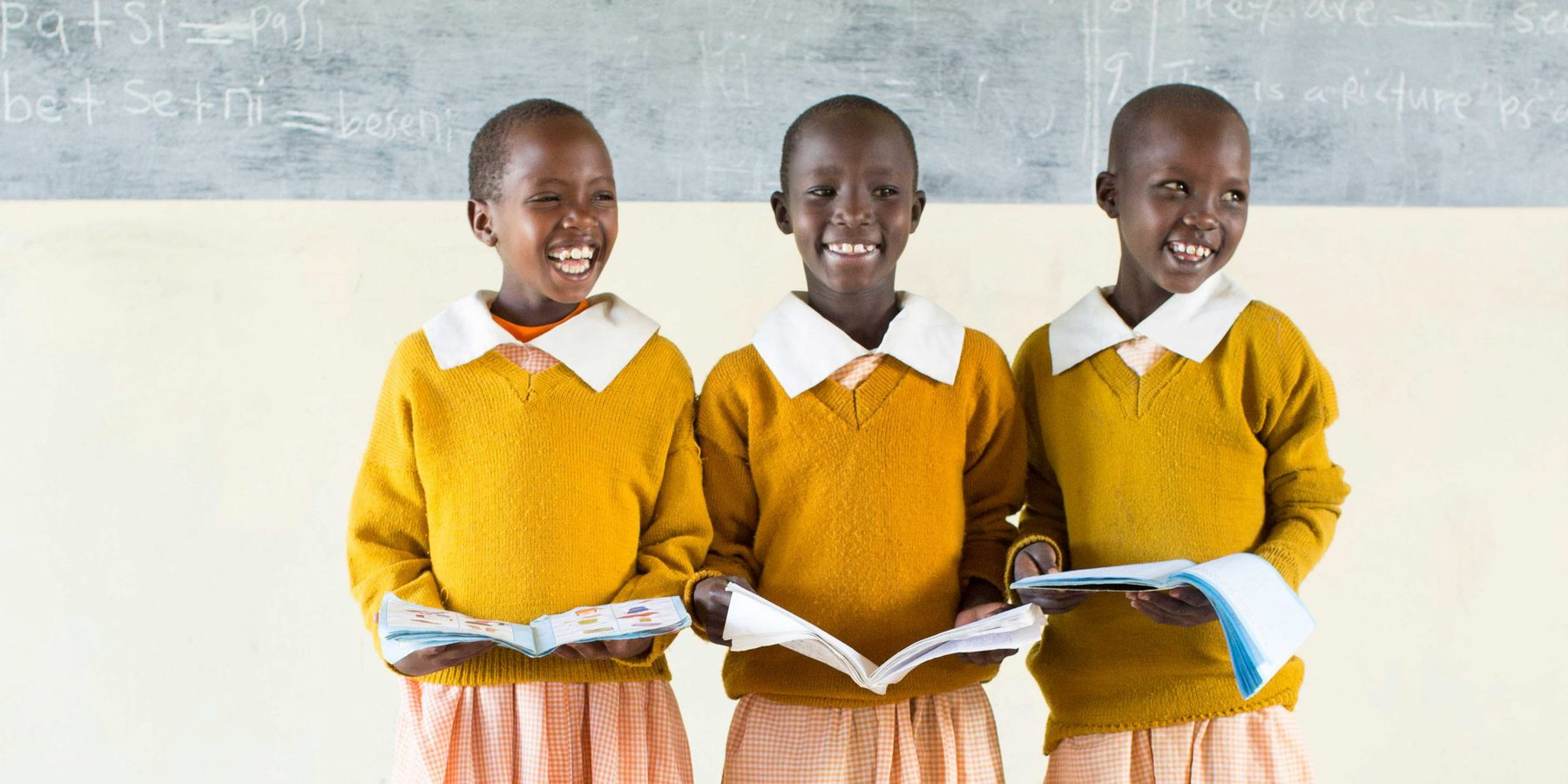 Three African girls in bright yellow sweaters laughing as they stand in front of the class presenting from their books.