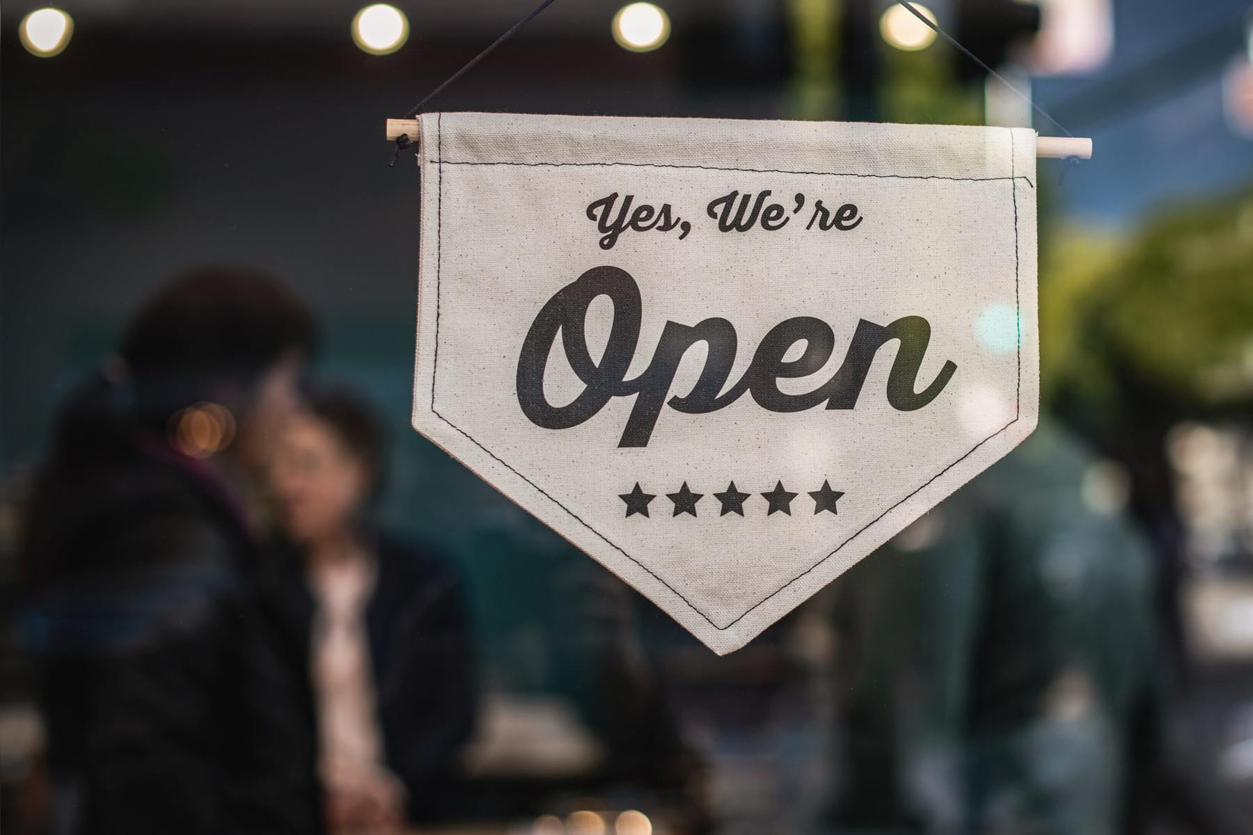 "A sign hanging in a store window saying ""Yes, We're Open"" with people shopping in the background"