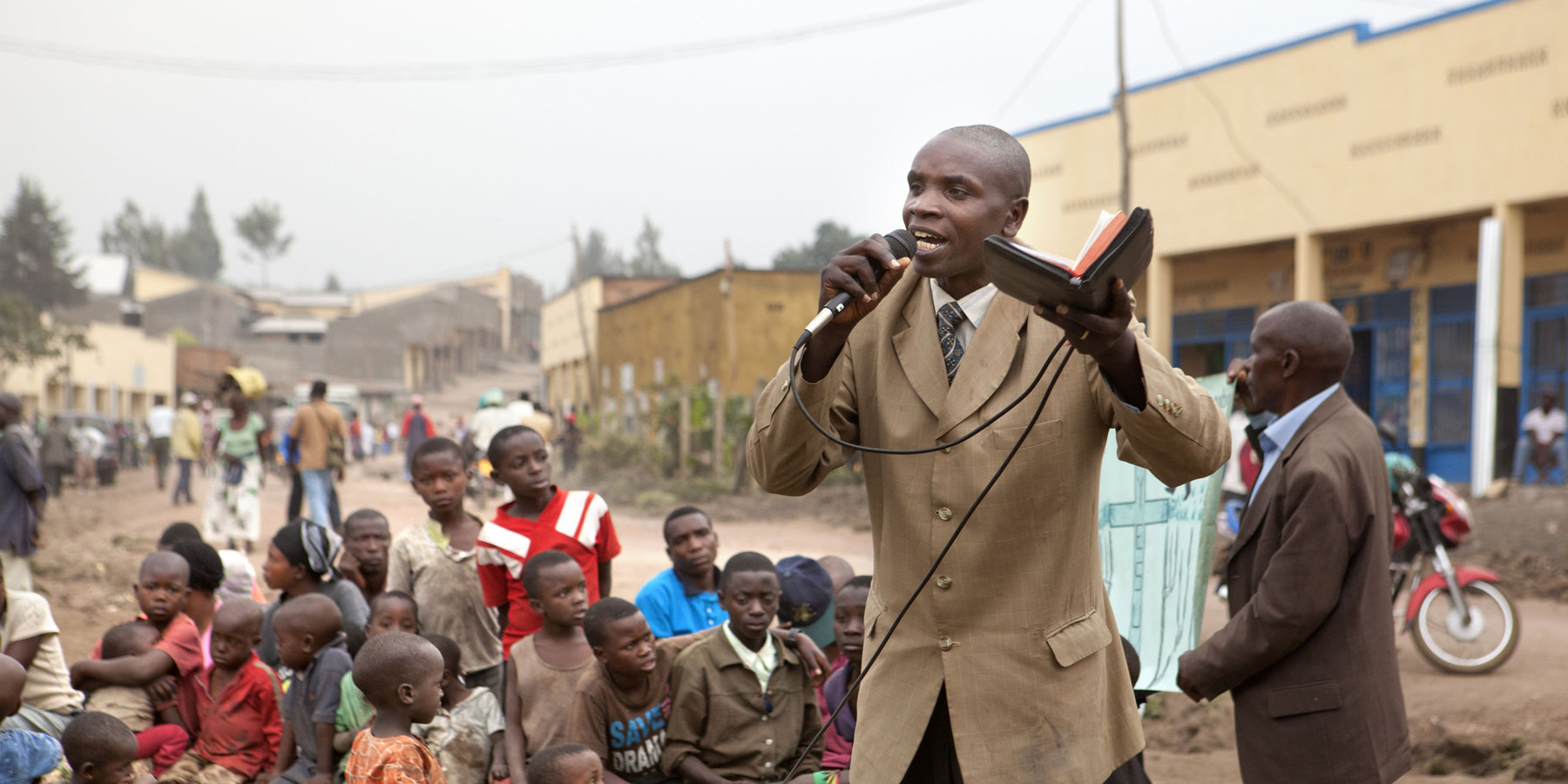 A Black man holding a Bible and a microphone, preaching to a group of children