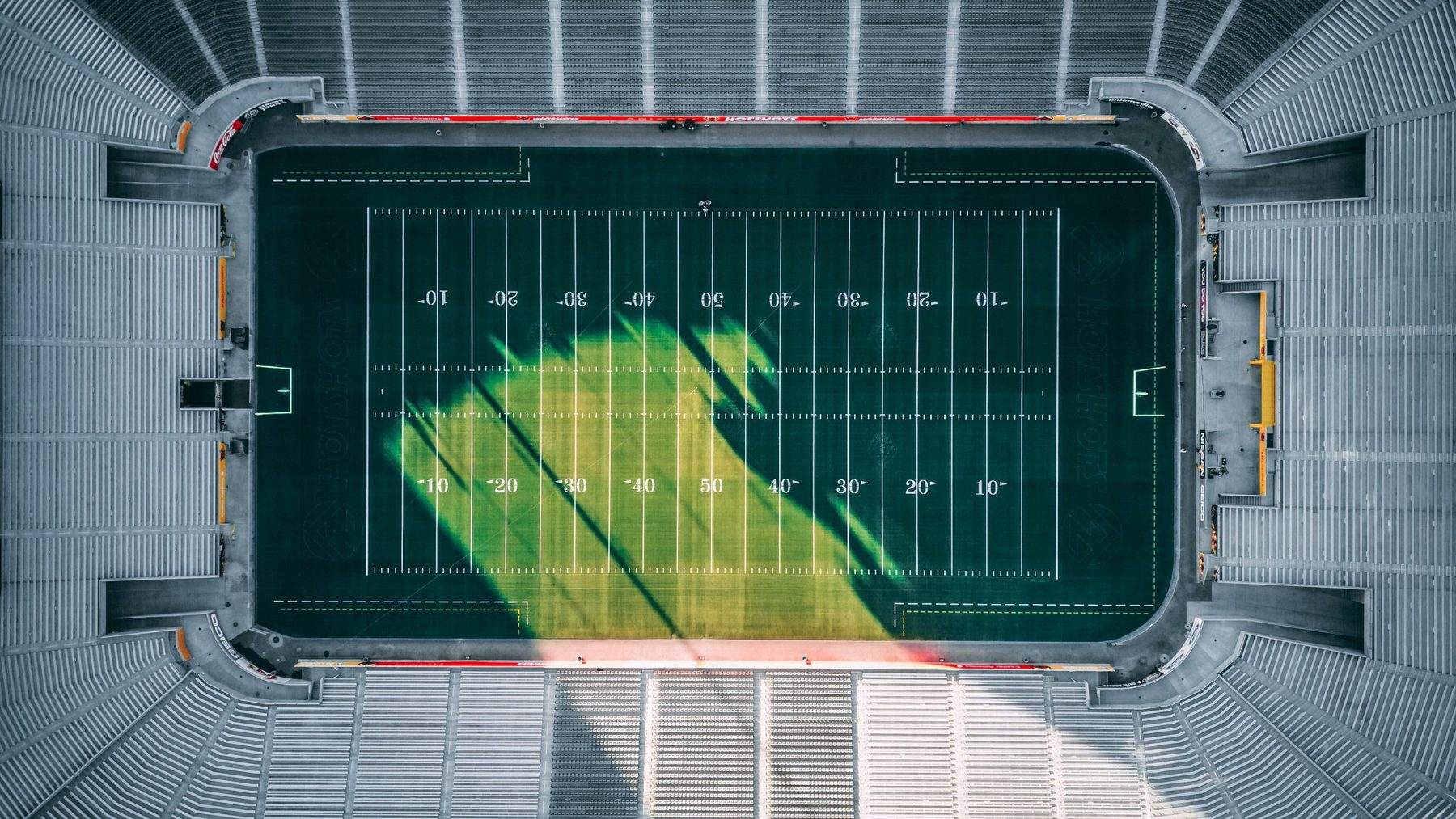 Sky view of a football field with an empty stadium surrounding it