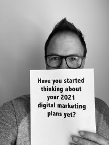 "Bob Hutchins with sign that says ""Have you started thinking about your 2021 digital marketing plans yet?"""